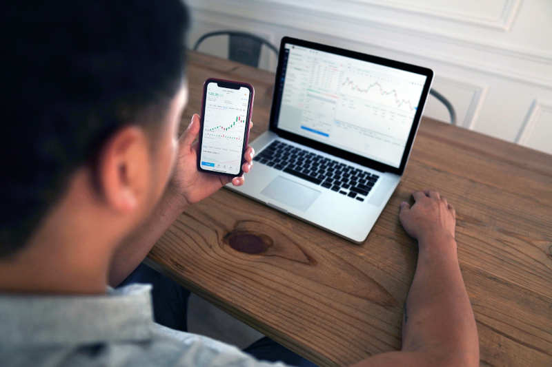 Trader at his notebook and smartphone trading online.