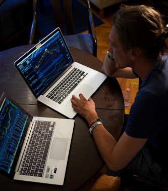 Junger Trader an zwei Notebooks